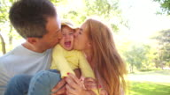 Parents affectionately kissing their little girl on both sides video