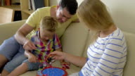 Parents and child playing fishing game at home video