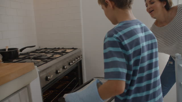 Parents And Children Baking Homemade Pizza In Oven video