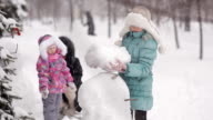 parents and children playing in the snow. Mom and daughter sculpt of snow in the winter woods. video