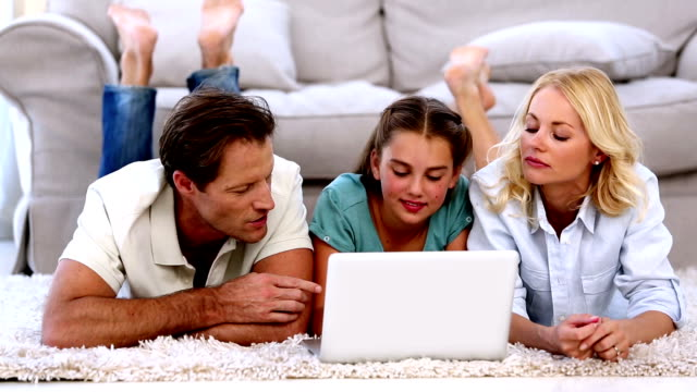 Parents and daughter happily using laptop on floor video