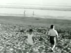 Parents and kids at the beach--From 1930's film video
