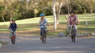 Parents and son cycling towards camera in a park video