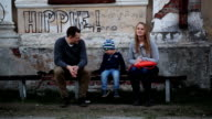 Parents and their child sitting on the bench near old video