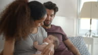 Parents Cuddling Baby Daughter In Bedroom At Home video