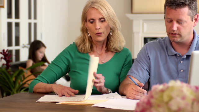 Parents Discuss Home Finances with Kids in Background video