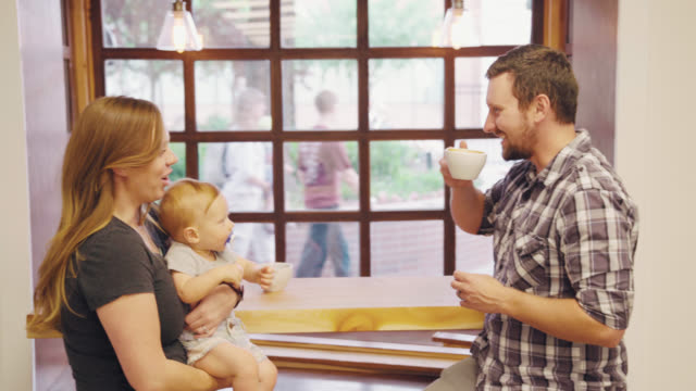 Parents Enjoy Coffee At Cafe With Baby video