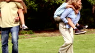 Parents giving piggy back rides to their children video