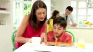 Parents Helping Children With Homework In Kitchen video