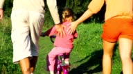 Parents helps daughter riding bicycle in summer park video