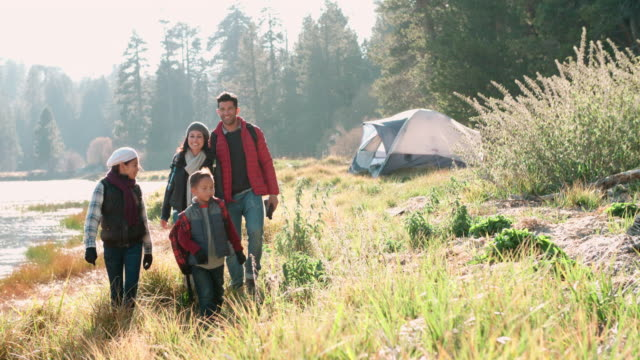 Parents on a camping trip with two kids walking near a lake video