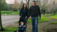 Parents on a walk pushing their little boy in a stroller, on a fall day video