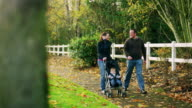Parents on a walk pushing their little boy in a stroller, talking and laughing video