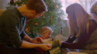 Parents opening presents with their baby in front of the tree on Christmas morning video