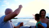 parents play with a child, family launches kite sitting in a boat, ride on the speed of the boat, a happy child laughing, mother, father and son spend time video