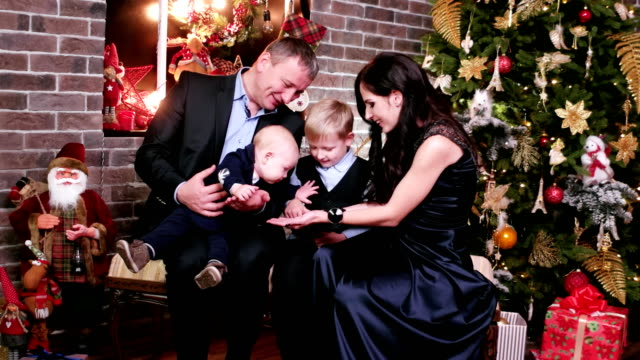Parents play with children, happy family New Year's eve, portrait of a happy family, mother, father and sons celebrating Christmas Eve video