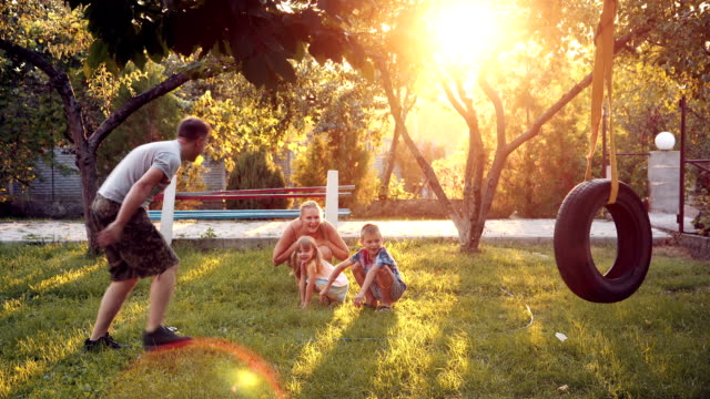 Parents playing with dog and children at home on backyard video