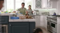 Parents Prepare Food As Children Play In Kitchen On R3D video