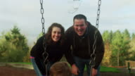 Parents smiling and making faces at their little boy on a swing video