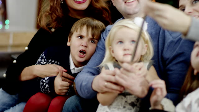 parents supporting girl holding selfie stick at christmas party video