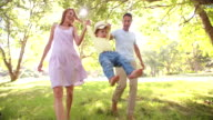 Parents swinging a little toddler girl towards the camera video