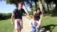 Parents Teaching Son To Ride Bike In Park video