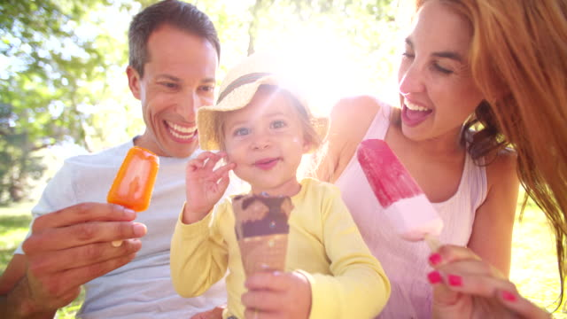 Parents with cheerful daughter and messy ice cream face video
