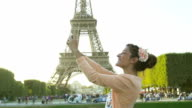 Paris, Young woman doing a Selfie with Eiffel Tower in background video