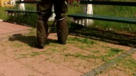 Park maintenance personnel mowing grass around two benches video