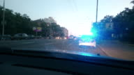 Parked police car with blue roof lights twirling, emergency, city video