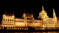 Parliament in Budapest at night while sailing on a boat on the river Danube. video