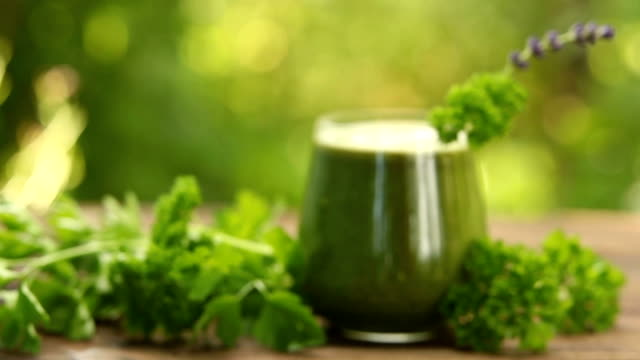 parsley and celery juice in glass on wooden table video