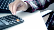 Part of woman hand using calculator on desk video