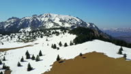 Partially snow covered alpine meadows in early spring, with scattered fir trees and snowy peaks panorama of the Ciucas mountains, middle Carpathian range, Romania, on a sunny beautiful day, aerial drone shot video