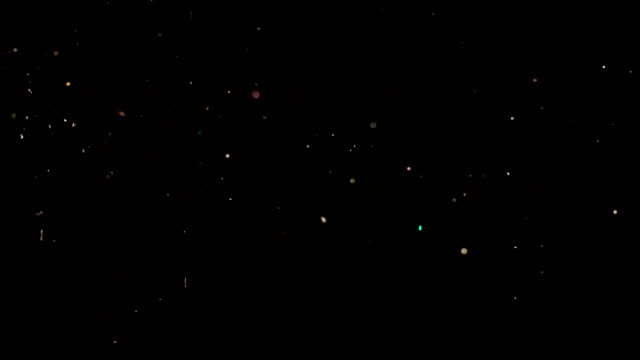 Particles flying on a black background. Colored particles flying erratically. video