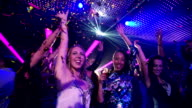 Party girls dancing and laughing with confetti in nightclub. video