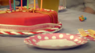 Party table and birthday cake with lit candles on it video