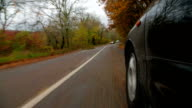 Passenger Car Moving Along Winding Road In Autumn Forest video