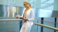 Passenger in a white pantsuit checks the tickets before departure video