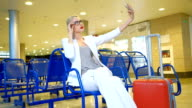 Passenger in waiting room at airport looking into phone indoors video