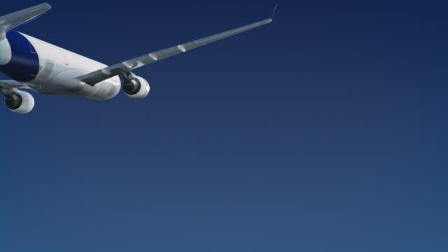 Passenger jet flying over clear blue sky - travel video