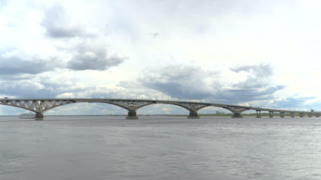 Passenger three-deck motor ship passes under a road bridge across the Volga river. Time-lapse recording. Summer day. Russia, city Saratov. Clip footage in 4K video