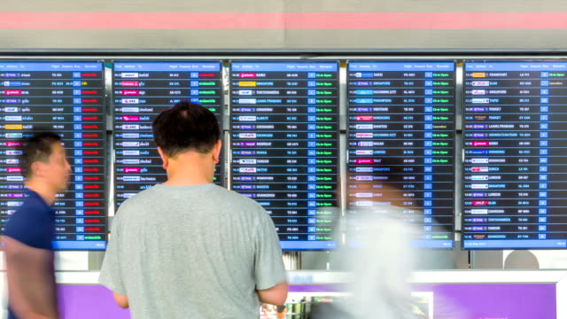 Passengers checking flights information on departure information signboard,Time Lapse video
