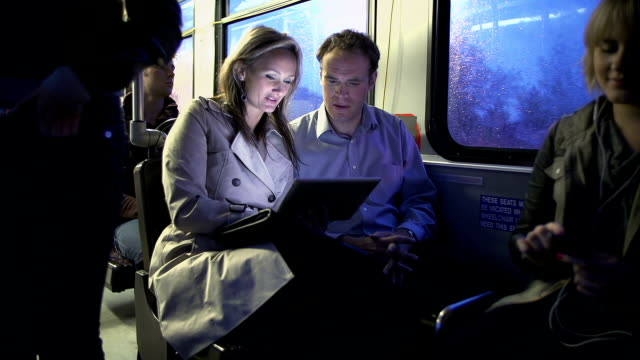 Passengers on a bus using digital tablet video