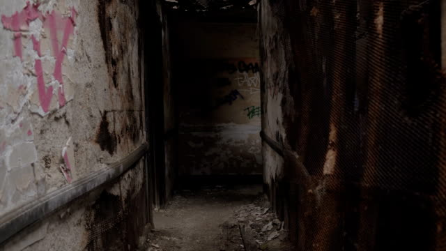FPV: Passing through narrow dark hallway in scary collapsing building in ruins video