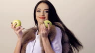 Passionate happy brunette posing and dancing with two green apples. Slowly video