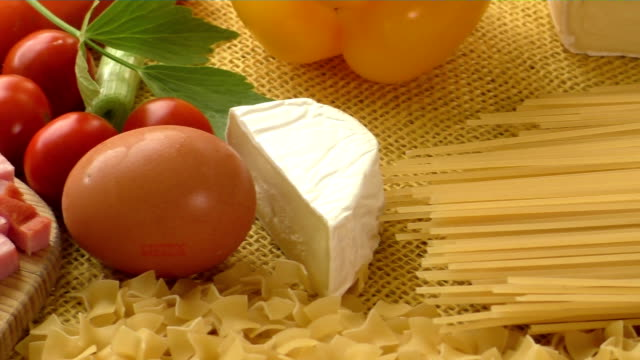 Pasta,ham,cheese,egg and vegetables with rustic sackcloth on yellow backgrounde video