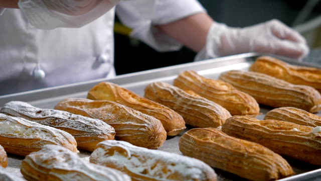 Pastry chef, dressed in a white chef's suit and transparent gloves sprinkle with powdered sugar from a special cup - a sieve to cook eclairs, standing on a metal tray video