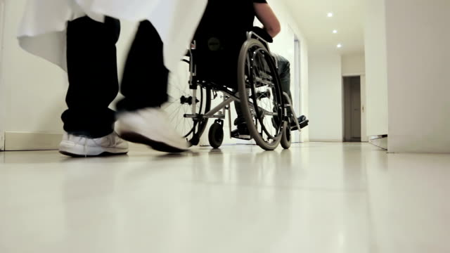 Patient in wheelchair being moved through hospital corridor video
