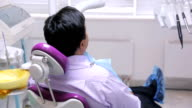 Patient ready for dental examination lying in a chair wearing glasses from ultraviolet video
